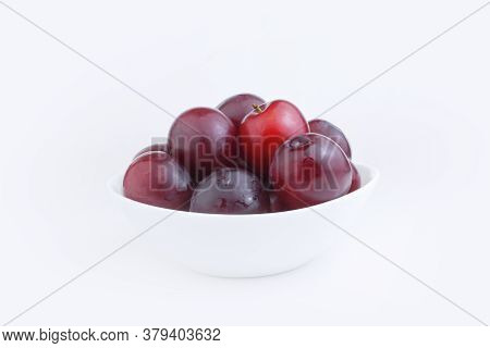 Fresh Blue Red Plums In A White Plate On A White Background. Harvest Plums Or Recipe For Plums. Copy