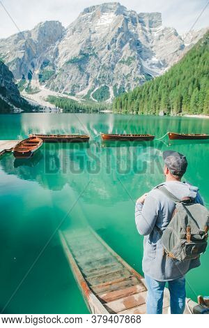 Man With Backpack Looking At Fabulous View Of Mountain Lake