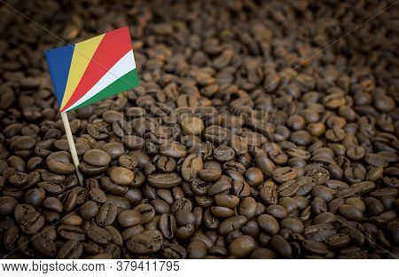 Seychelles Flag Sticking In Roasted Coffee Beans. The Concept Of Export And Import Of Coffee