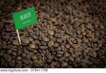 Saudi Arabia Flag Sticking In Roasted Coffee Beans. The Concept Of Export And Import Of Coffee