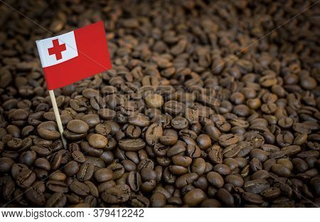 Tonga Flag Sticking In Roasted Coffee Beans. The Concept Of Export And Import Of Coffee