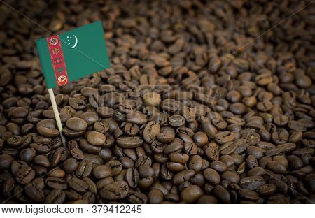 Turkmenistan Flag Sticking In Roasted Coffee Beans. The Concept Of Export And Import Of Coffee