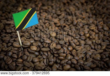 Tanzania Flag Sticking In Roasted Coffee Beans. The Concept Of Export And Import Of Coffee