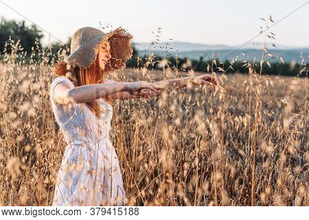 Portrait Of Young, Teen, Ginger Girl With Freckles In The Wheat Field Wearing A Summer Hat, Dancing.