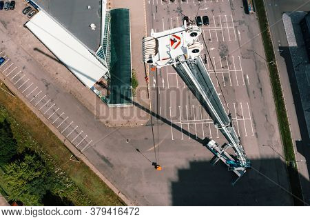 View From The Height Of The Car Of A Heavy Crane With A Cradle, Which Is Open In The Parking Lot And