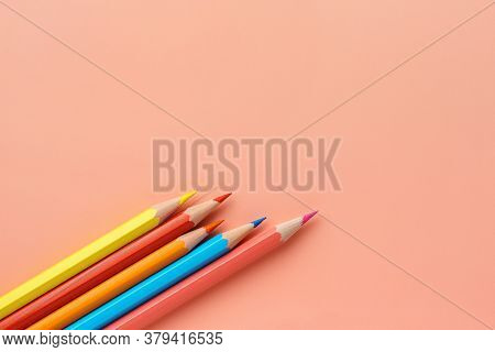Colorful Pencils On Pink Pastel Background, Flat Lay. Uneven Set Of Rainbow Pencils, Copy Space. Pen