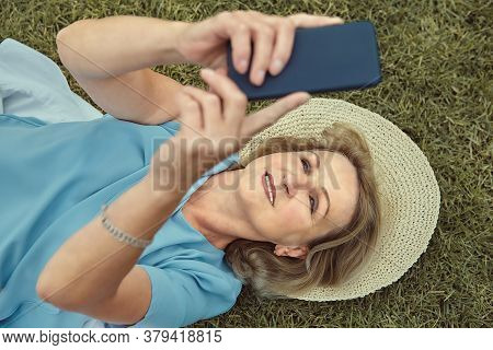 Elderly Caucasian Attractive Woman About 60 Years Old Is Smiling While Lying Down The Grass Outdoor