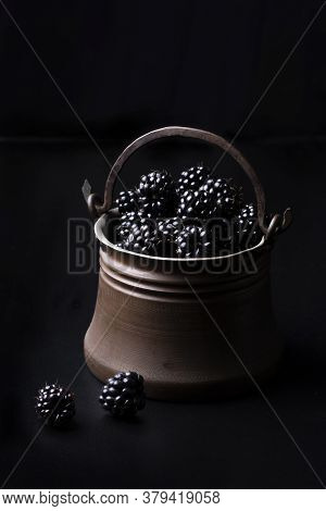 Ripe Blackberries In Bucket On Dark Background