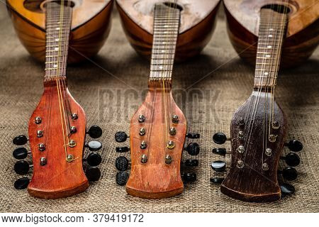 Three Old Mandolins Rotated Fingerboards To The Camera. On A Background Of Rough Burlap Texture.