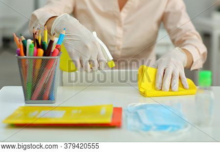 A Girl In A Medical Gloves Treats And Disinfects Surfaces And School Before Classes . Table With Stu