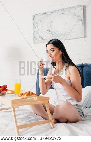 Focus Of Asian Woman Drinking Coffee Near Breakfast On Breakfast Tray On Bed