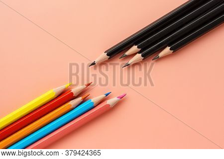Set Of Colored Pencils Lie Opposite Black Pencils On Pink Pastel Background, Flat Lay. Pencils Lie D
