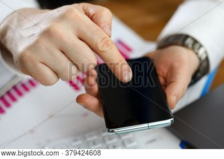 Man Holds Smartphone Leaning On Financial Report. Indicators Existing Advertising Campaigns. Setting