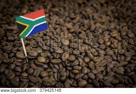 South Africa Flag Sticking In Roasted Coffee Beans. The Concept Of Export And Import Of Coffee