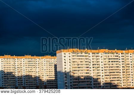 Gloomy Dark Rain Clouds Over The Sunlit Multi-storey Panel Houses. Russia, Contrast, Bad Weather And