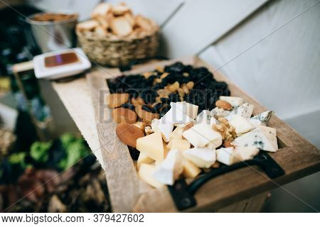 Cheese, Dried Fruits And Nuts On A Wooden Board In A Restaurant On The Wedding Table. Catering Servi