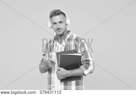 Handsome University Tutor Pointing Finger. Adult Student Hold Notebook. Man With Folder In Headphone