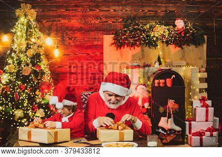 Santa Helper With Santa Claus Holding Christmas Gift With Presents. Merry Christmas And Happy New Ye