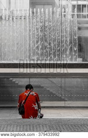 A Man In A Red Shirt Sits In Front Of A Fountain, Image Of Street Photography With Selective Desatur