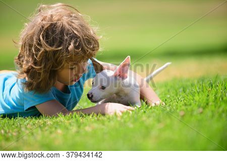 Cute Boy Child With Her Doggy Lying On Lawn. Kids With Her Pet Friend
