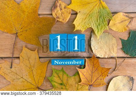 November 11th. Blue Cube Calendar With Month And Date On Wooden Background.
