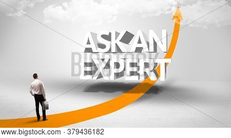 Rear view of a businessman standing in front of ASK AN EXPERT inscription, successful business concept