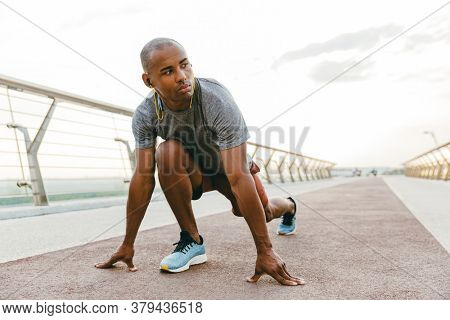 Young african man jogger exercising outdoors on a bridge, getting ready to start running
