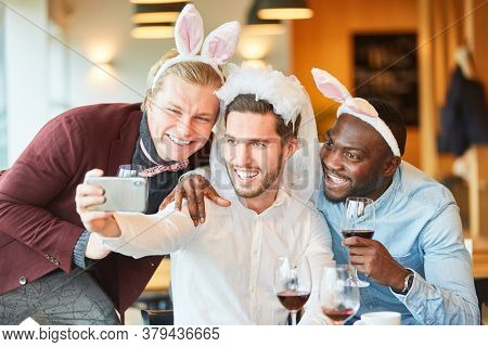 Friends at bachelor party in funny disguise take a selfie