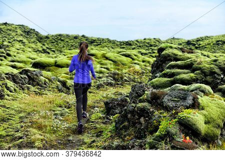 Running woman athlete trail runner - running woman exercising. Fit female sport fitness model training jogging outdoors living healthy lifestyle in beautiful nature, Iceland.