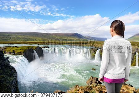 Iceland Travel. Tourist woman by Godafoss waterfall. Happy young woman tourists enjoying icelandic nature landscape visiting famous tourist destination attraction, Iceland.