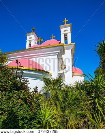 Gorgeous green south park.  Israel. Capernaum. Place of worship and pilgrimage. Snow-white church with pink domes and golden crosses. The concept of religious pilgrimage and photo tourism