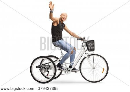 Profile shot of a bald guy riding a tricycle and waving at the camera isolated on white background