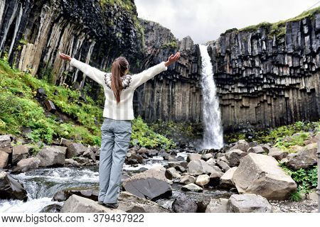 Iceland. Woman enjoying majestic Svartifoss waterfall. Female is visiting famous tourist attraction of Iceland. Spectacular natural landmark on vacation in Skaftafell. Icelandic nature landscape.