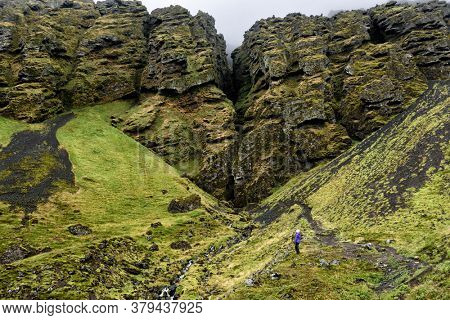 Iceland hiker tourist sightseeing visiting Raudfeldsgja Canyon gorge rift nature landscape on the Snaefellsnes peninsula, West Iceland.