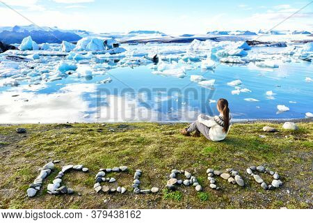 Iceland nature landscape Jokulsarlon glacial lagoon - ICELAND text written with rocks. Woman enjoying view visiting tourist destination landmark attraction glacier lake, Iconic Vatnajokull.