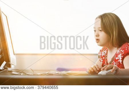 Girl with Down syndrome using computer at school