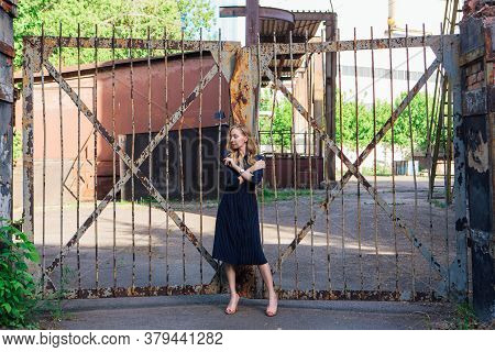 Fashion Looks Woman Near The Old Rusty Gate. Young Woman Modern Portrait.