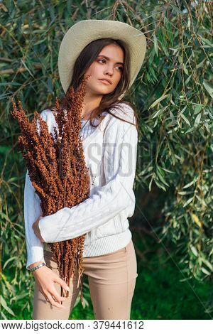 Young Beautiful Brunette Woman Standing Close To The Tree Brunches With Green Leaves Holding Dry Bou