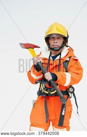 A Portrait Of Asian Male Fireman In Red Protective Clothing, Mask And Helmet With An Ax Standing On