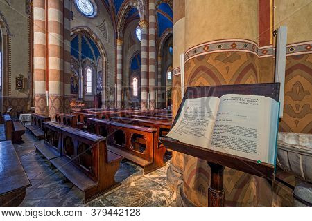 ALBA, ITALY - JUNE 14, 2020: Holy book on the stand as wooden pews and columns on background inside of San Lorenzo cathedral aka dedicated to Saint Lawrence in small town of Alba in Piedmont, Italy.