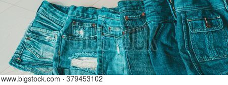 Jeans shorts layered by shades of blue indigo dye. Different styles of distressed denim fashion textile fabric banner panoramic.