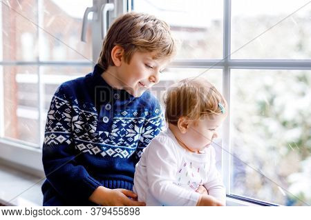 Happy Adorable Kid Boy And Cute Baby Girl Sitting Near Window And Looking Outside On Snow On Christm