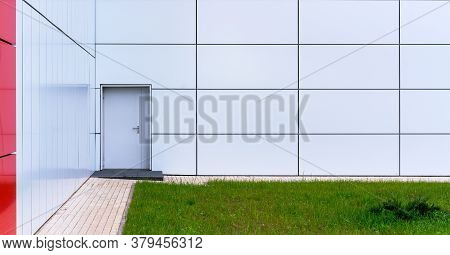 White Wall With Grey Door Near Panoramic Windows With Red Decorative Line At Paved Sidewalk And Gree