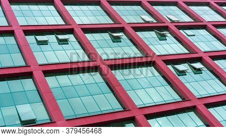 Fashionable Office Building Wall With Red Beams And Panoramic Windows Reflecting Blue Skyscape On Su