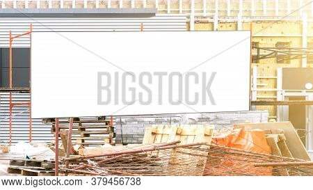 White Empty Ad Banner With Place For Template Fixed On Grey Building Scaffold And Metal Grid Debris