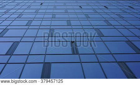 Commercial City Building With Panoramic Windows And Black Decorations Reflects Blue Skyscape On Sunn