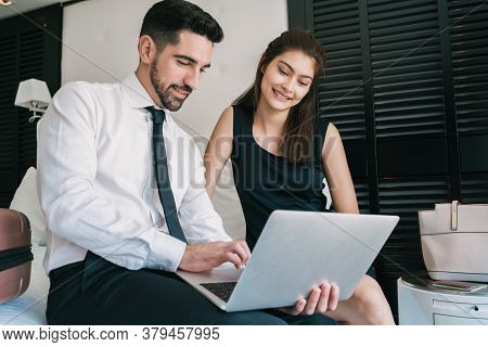 Portrait Of Two Young Business People Working Together On The Laptop At The Hotel Room. Business Tra