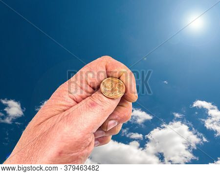 Hand With Coins On A Background Of Blue Sky. God's Gift. Prayer. Request For Help. They Ask For Mone