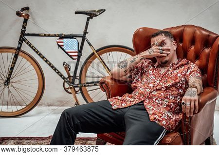 Very Expressive And Stylish Guy In Hawaiian Shirt And Sunglasses Relaxing On A Luxury Retro Sofa Loo
