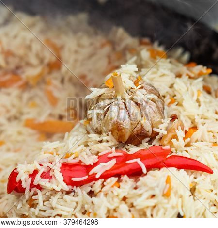 Cooking Pilaf Rice In A Large Cast Iron Pot Over The Fire. Garlic Bulb And Red Hot Pepper
